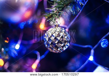 ball toy on branch of Christmas tree for new year with blurred colorful background of lights garland fortraditional new year