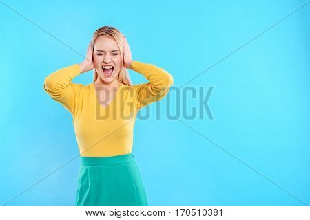 What a terrible noise. Irritated young woman is closing her ears by hands and shouting. Her eyes are closed with desperation. Isolated and copy space in right side