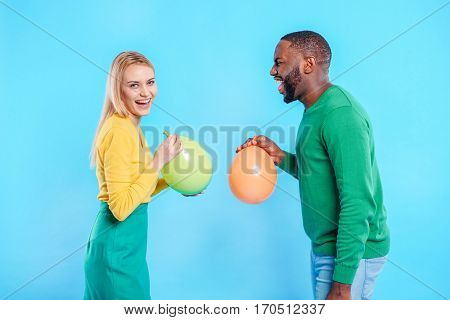 Joyful young african man and caucasian woman are inflating colorful balloons. They are standing and laughing. Isolated on blue background