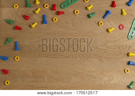 Kids construction toys tools: colorful screws and nuts on wooden background. Top view. Flat lay. Copy space for text