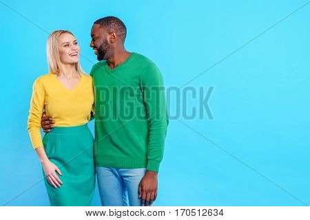 Joyful man and woman are embracing. They are standing and smiling. Isolated and copy space in right side