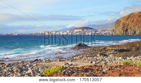 Stony beach and Las Americas and Los Cristianos towns in the background, Tenerife Island, Canaries