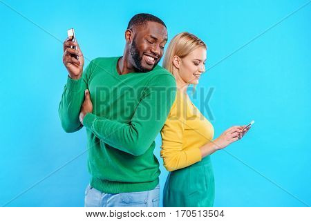 What are you doing. Smiling young woman is messaging on smartphone. Man is standing and looking at her gadget with interest. Isolated on blue background