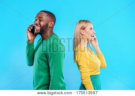 Joyful modern couple is talking on mobile phones instead of real communication. They are standing and laughing. Isolated