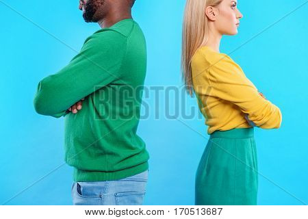 Sad young couple is offended at each other. They are standing with crossed arms. Isolated