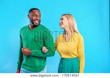 Happy couple is standing and holding hands. Woman is looking at man with love and smiling. Isolated