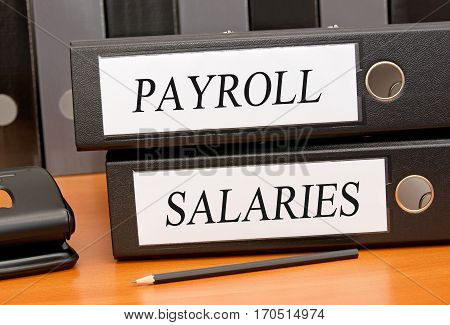 Payroll and Salaries - two binders on desk in the office
