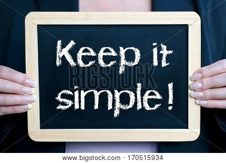 Keep it simple - Businesswoman holding chalkboard with text