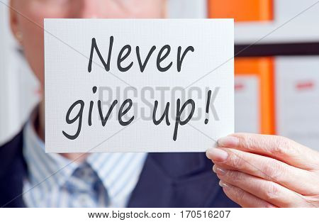 Never give up - Businesswoman with sign in the office