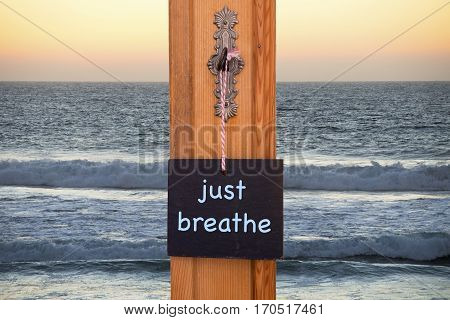 small blackboard with the words Just Breathe hanging on key in front of the ocean