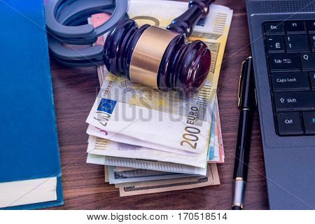 Wooden hammer handcuffs and euro bills laptop on desk.