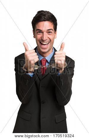 Happy businessman wearing handcuffs