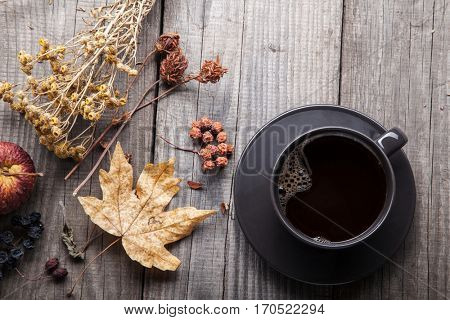 cup of hot espresso among autumn plants on wooden vintage table, coffee on the old board grunge including dried plants, top view