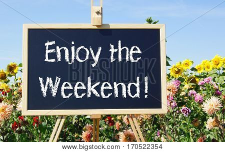 Enjoy the Weekend - easel with chalkboard in the summer garden with flowers