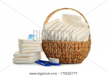 Baby diapers in wicker basket and necessities on white background