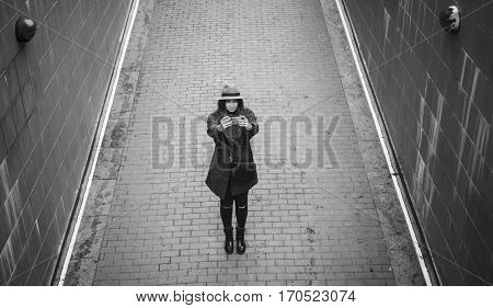 Young woman in a hat and coat, photographing on a smartphone, amid pavement top view. Girl holding a device with both hands