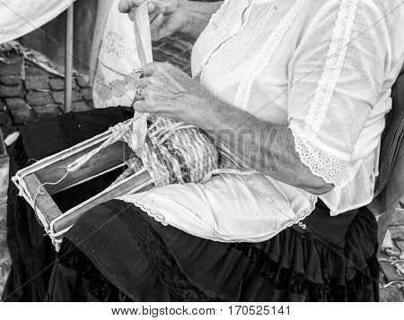 Elderly lady builds bags woven by hand using the dried leaves of the corn cobs.