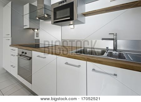 modern kitchen counter with built in appliances and hard wood worktop