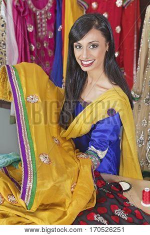 Portrait of an Indian female dressmaker holding sari