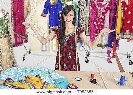 Portrait of Indian female dressmaker with hand gestures at design studio
