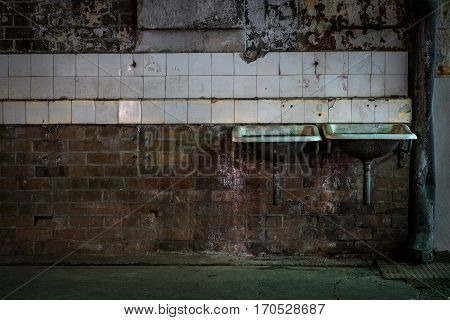 Two industrial sinks on tiled brick wall in abandoned warehouse