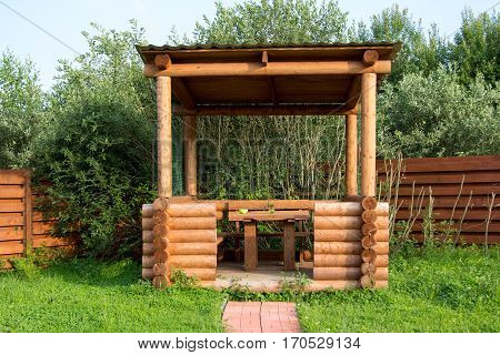 wooden table and benches in a log arbor
