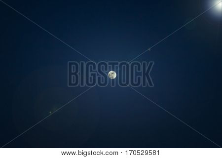 The full moon with dark spots: on the background of the pure dark blue sky. Heavenly light, with reflections on the lens