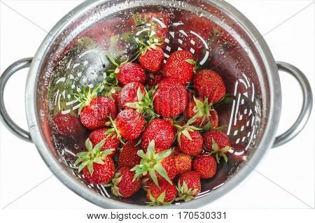 Fresh ripe strawberries in a colander top view