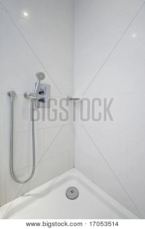 detail shot of a corner shower with designer wall mount water tap