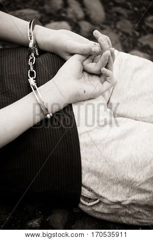 Young Boy Lying Handcuffed On The Ground