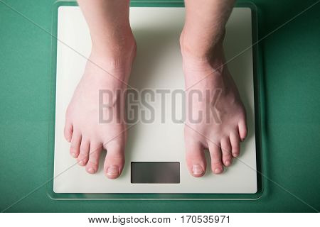 Young Boy Weighing Himself On A Scale