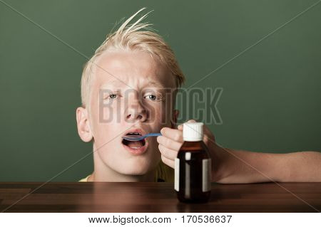 Sick Young Boy Taking Oral Medication