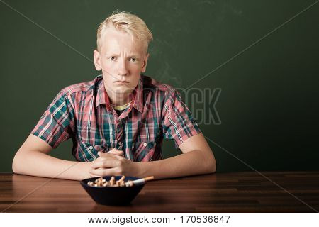 Frowning Defiant Teenage Boy With Cigarettes