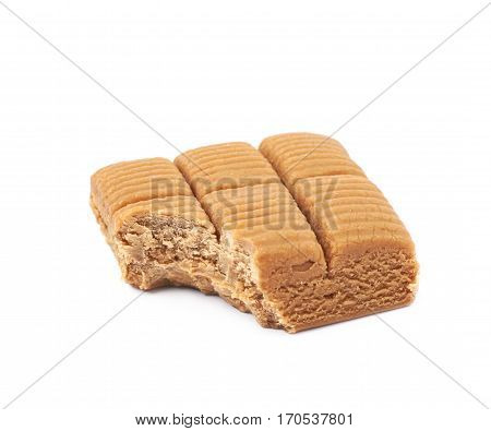 Toffee confection bar with a bite taken off it, composition isolated over the white background