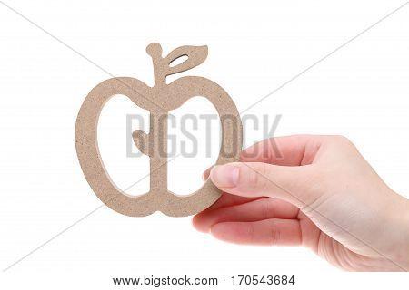 Hand holding imitation of wooden apple on white background