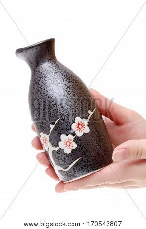 Hand holding japanese sake bottle isolated on white background