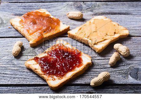 nut nougat cream with chocolate strawberry apricot jam and peanut butter sandwich