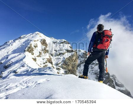 Hiker looks at a winter mountain landscape. European Alps.