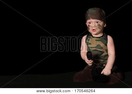 Baby Soldier In Uniform With War Paint On His Face. Boy In Uniform Against The Black Background.
