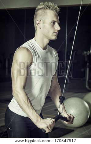 Young handsome man training triceps, on gym equipment, pulling handle on cables