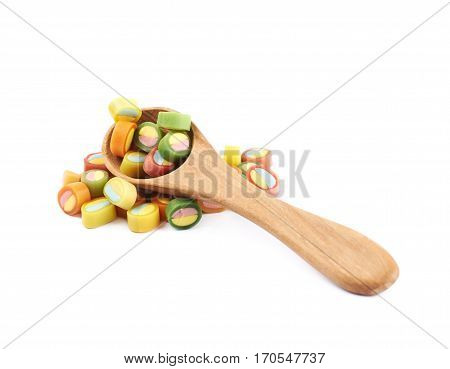Pile of multiple colorful licorice candies with the wooden spoon over it, composition isolated over the white background