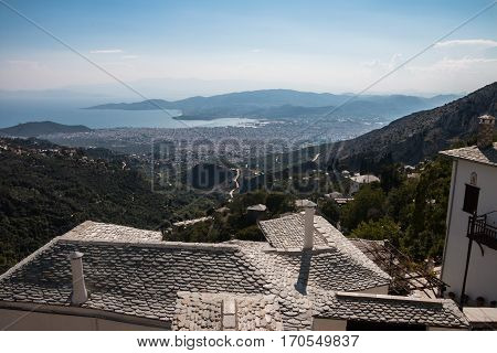 View from above slate roofs, down to a bay with the town of Volos