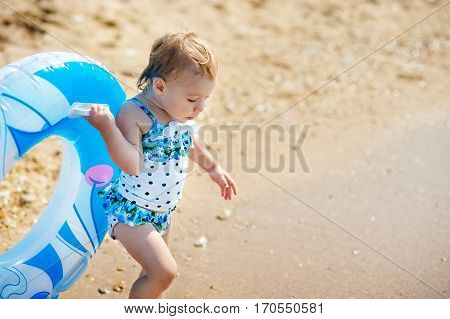 Little girl in swim suit with swimming circle ready to go into the sea at early sunset. Summer fun.