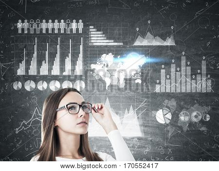 Girl In Glasses And Graphs On Blackboard