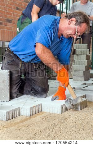 Builder laying paving stones for an outdoor patio around a house with his team of workmen close up view of him tamping a brick with a mallet
