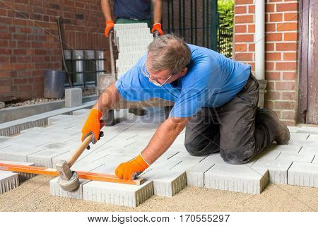 Builder Levelling Paving Stones As He Lays Them
