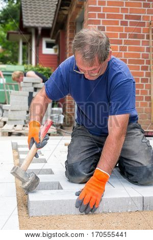 Workman laying new paving stones for a patio on a residential property tamping them into position with a heavy mallet or hammer