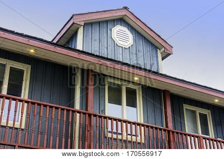 Quaint painted country house with wooden siding and large balcony top floor view with sky