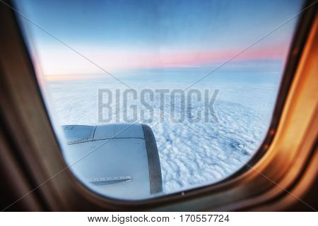 huge fields and small town seen through the window of jet airplane in bright sunny day