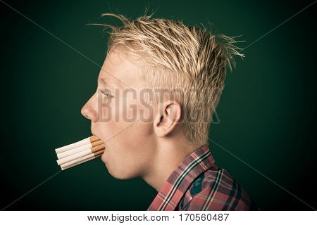 Young Boy With A Mouthful Of Cigarettes